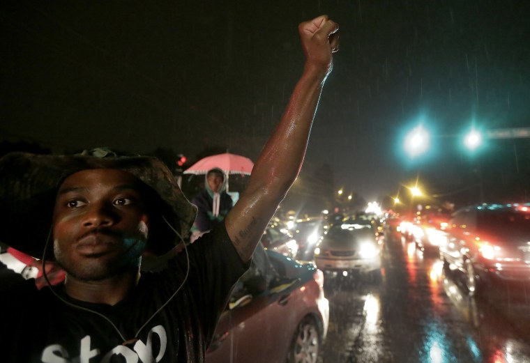 A protester holds up a clenched fist Friday, Aug. 15, 2014, in front of a convenience store that was looted and burned following the shooting death of...