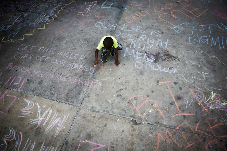 A young boy uses sidewalk chalk to draw on a parking lot filled with memorial slogans during a demonstration to protest the shooting of Michael Brown and the resulting police response to protests, in Ferguson, Mo, Aug. 15, 2014.
