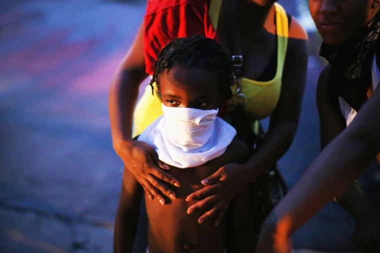 A child uses a rag to shield his face from tear gas being fired by police who used it to force protestors from the business district into nearby neighborhoods on Aug. 11, 2014 in Ferguson, Mo.