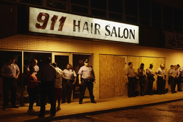 Police officers stand in position by the 911 Hair Salon as they watch demonstrators protest Michael Brown's murder, Aug. 16, 2014 in Ferguson, Mo. Missouri Governor Jay Nixon and Missouri State Highway Patrol Captain Ronald Johnson imposed a 12am curfew for demonstrators continuing to protest the the killing of Brown, who was shot and killed last week by Ferguson Police Officer Darren Wilson after being suspected in taking part in a robbery at a convenience store.