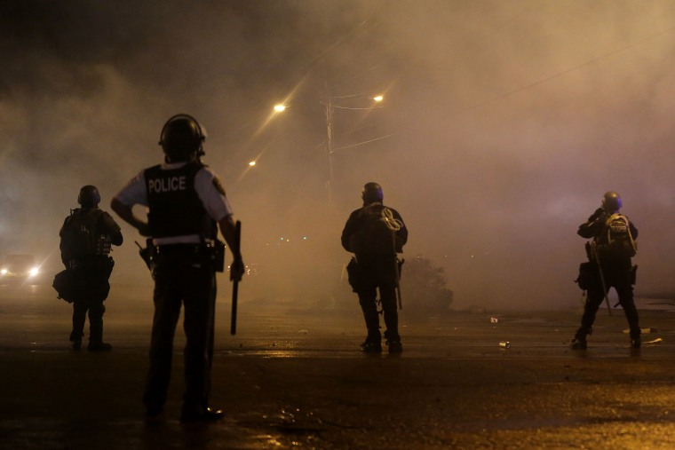 A law enforcement officer watches Sunday, Aug. 17, 2014, as tear gas is fired to disperse a crowd protesting the shooting of teenager Michael Brown last Saturday in Ferguson, Mo.