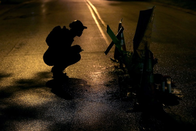A woman pauses, Aug. 15, 2014, before a makeshift memorial in the middle of the street where Michael Brown was killed by police Aug. 9 in Ferguson, Mo.