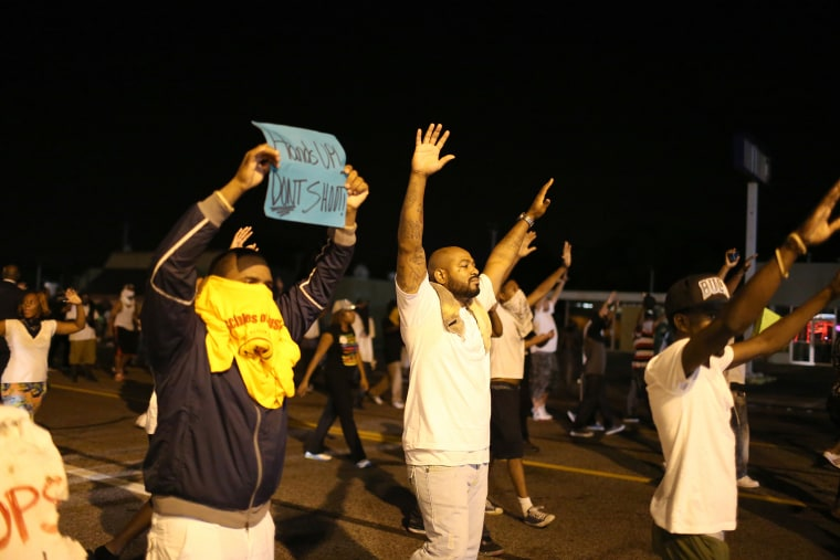 "Demonstrators raise their arms and chant, ""Hands up, Don't Shoot"", as police clear them from the street as they protest the shooting death of Michael Brown on Aug. 17, 2014 in Ferguson, Mo."