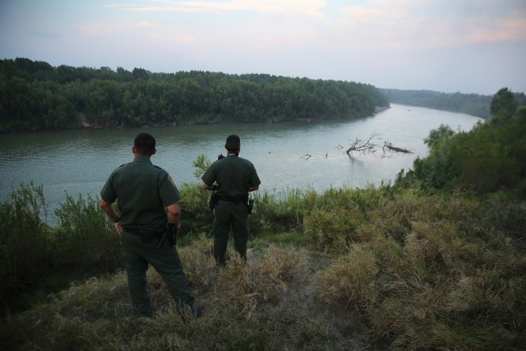 U.S. Border Patrol agents look for immigrants crossing the Rio Grande from Mexico (L), to the United States at dusk on July 24, 2014 near Mission, Texas.