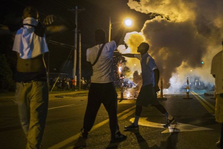 Protesters involved with a more vocal and confrontational group of demonstrators stand and gesture as tear gas is fired, at further protests in reaction to the shooting of Michael Brown near Ferguson, Missouri August 18, 2014.
