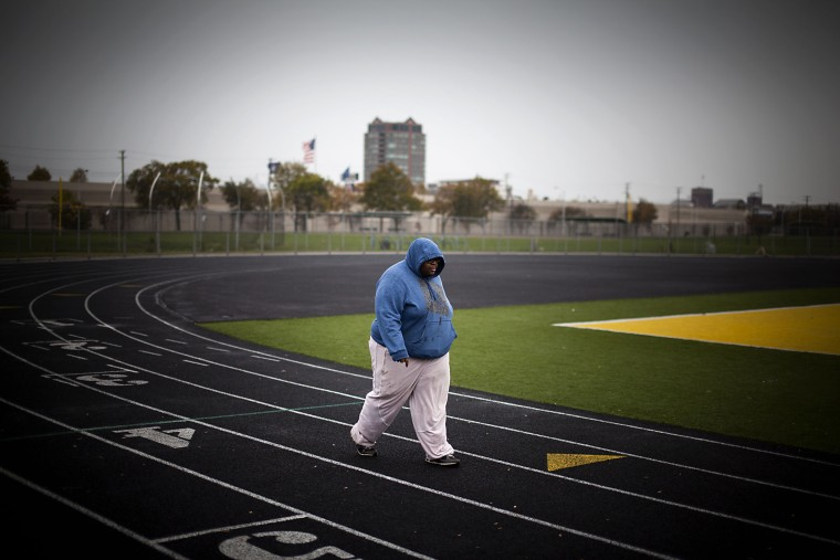 A young man exercising on a running track surrounding a football field in Detroit, Michigan, October 14, 2012.