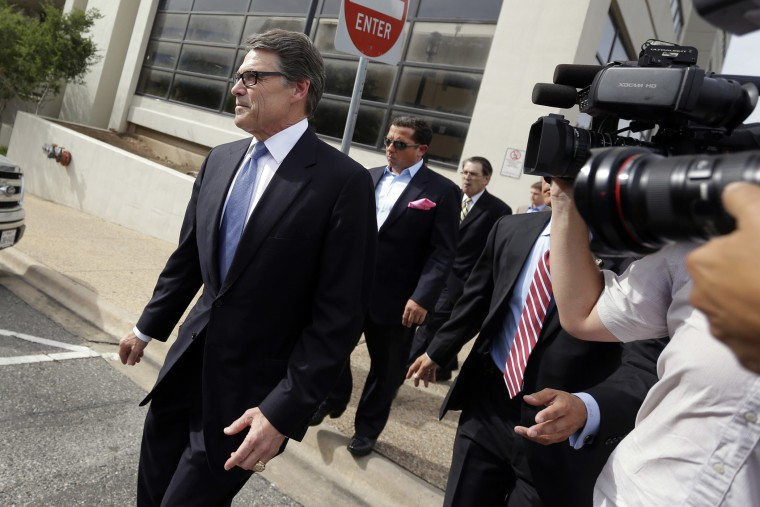 Texas Gov. Rick Perry, left, leaves the Blackwell Thurman Criminal Justice Center after he was booked, Tuesday, Aug. 19, 2014, in Austin, Texas.