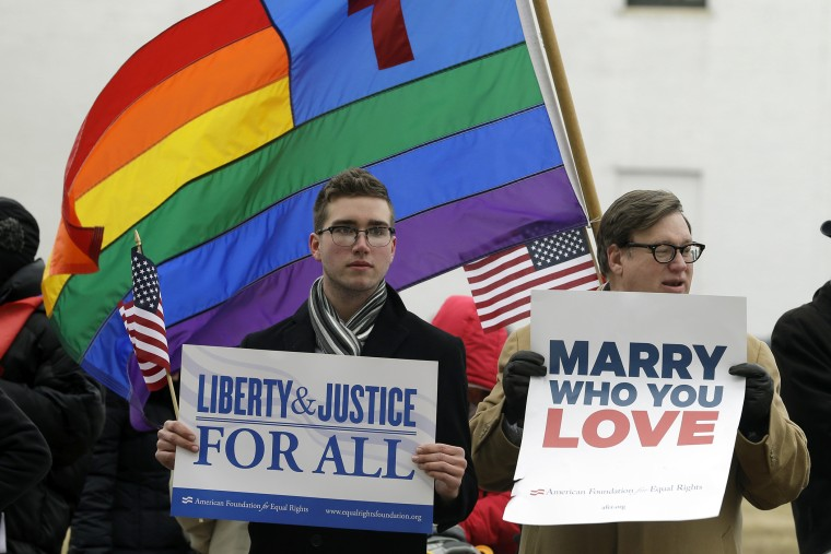 Spencer Geiger, left, of Virginia Beach, and Carl Johanson, of Norfolk, hold signs as they demonstrate outside Federal Court in Norfolk, Va. on Feb. 4, 2014