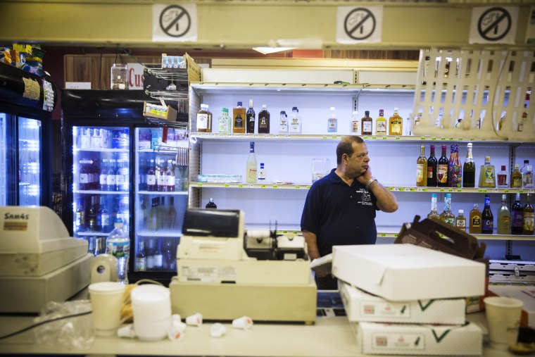 Sam's Meat Market & More employee Steve Sumad rubs his neck as he surveys damage caused by looters the night before in Ferguson, Missouri, August 16, 2014.
