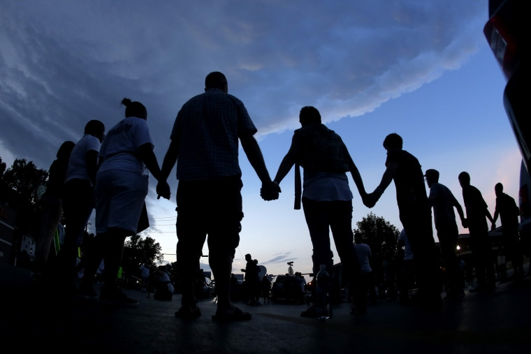 People stand in prayer after marching about a mile to the police station to protest the shooting of Michael Brown Wednesday, Aug. 20, 2014, in Ferguson, Mo.