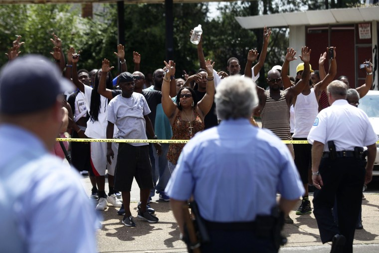 A crowd reacts to St. Louis Police Officers standing outside Golden Shears Barber & Beauty Shop where officers shot a man holding a knife in St. Louis, Mo., Aug. 19, 2014.