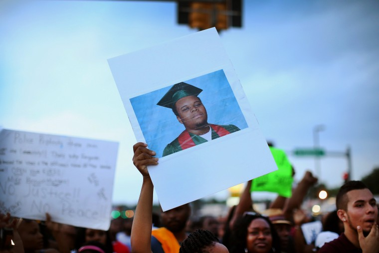 A demonstrator carries a picture of Michael Brown during a protest along Florissant Avenue on Aug. 16, 2014 in Ferguson, Mo.