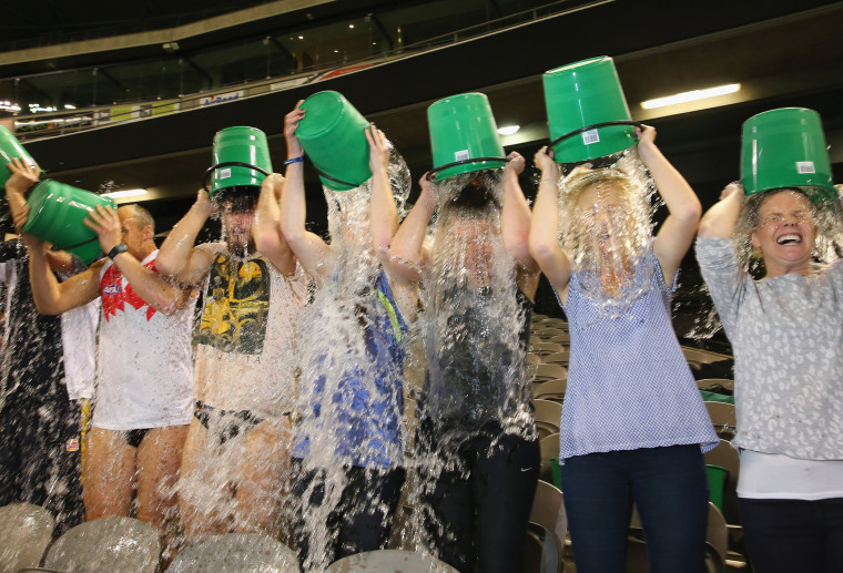 Participants tip buckets of ice water over their heads as they take part in the World Record Ice Bucket Challenge at Etihad Stadium on August 22, 2014 in Melbourne, Australia.