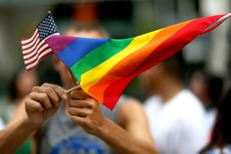 A protester holds an American flag and rainbow flag.
