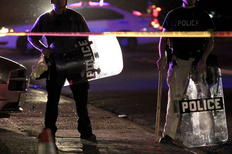 Police wearing riot gear stand at a post as they wait for a crowd to disperse, Aug. 11, 2014, in Ferguson, Mo.