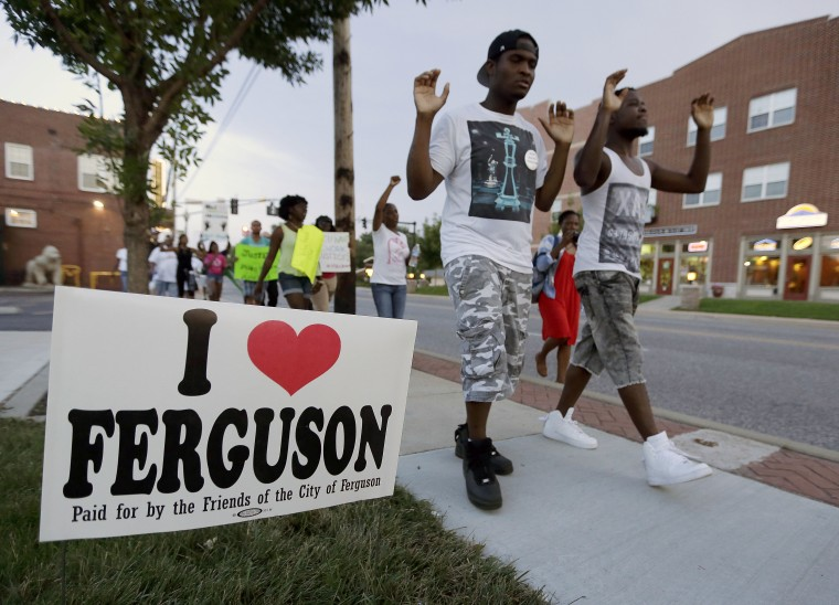 FILE - In this Aug. 20, 2014 file photo, people march to protest the shooting of Michael Brown in Ferguson, Mo. Residents who live near where Brown was shot...