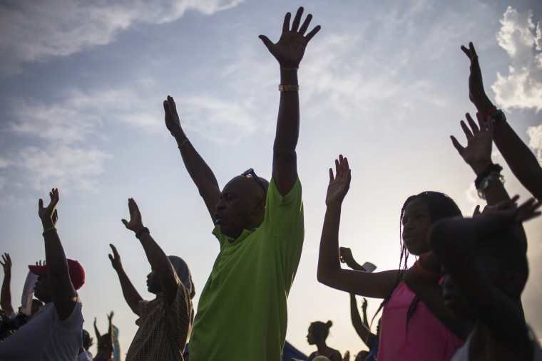 Supporters of Michael Brown, who was killed by a police officer on August 9, raise their hands in solidarity as they are led by Tracy Martin, father of Trayvon Martin, a Florida teenager shot dead in 2012, at the the Peace Fest 2014 rally in St. Louis, Mo