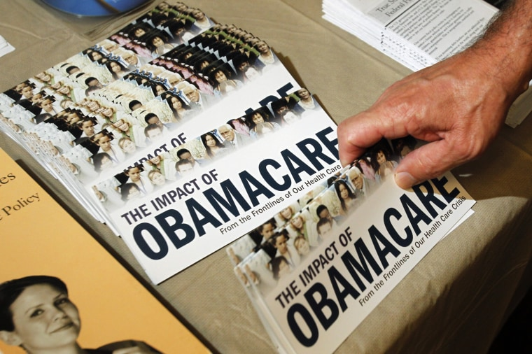 """A Tea Party member reaches for a pamphlet titled \""""The Impact of Obamacare\"""", at a \""""Food for Free Minds Tea Party Rally\"""" in Littleton, New Hampshire in this October 27, 2012. (Photo by Jessica Rinaldi/Reuters)"""