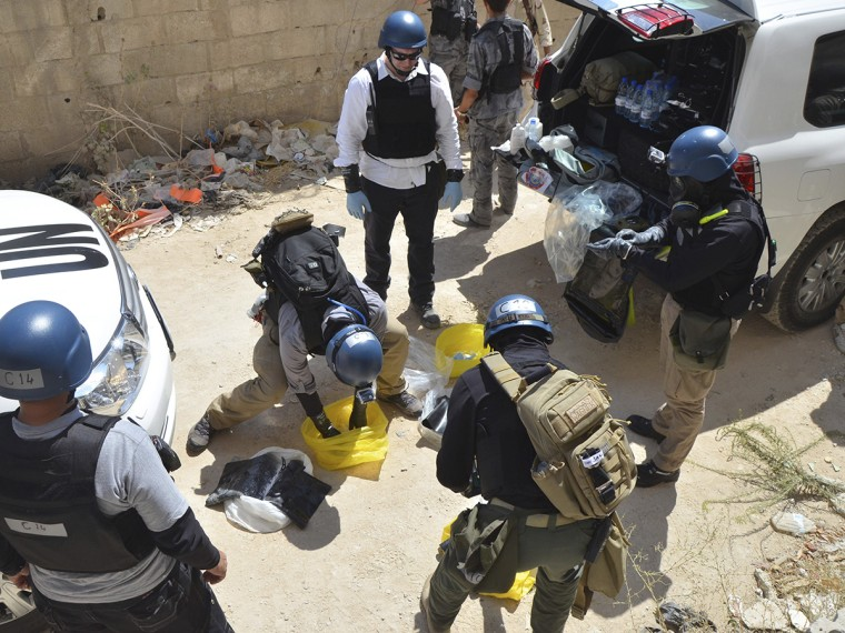 U.N. chemical weapons experts prepare before collecting samples from one of the sites of an alleged chemical weapons attack in Damascus' suburb of Zamalka August 29, 2013.