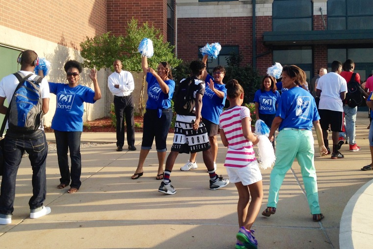 Volunteers from the Spirit Church, which holds services at McCluer South-Berkeley High School in Ferguson, Mo., welcome students at the start of school on Aug. 25, 2014.