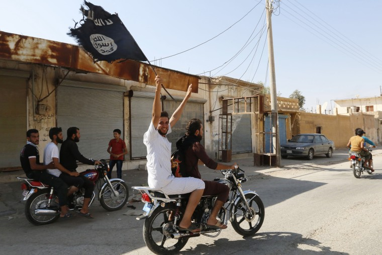 A resident of Tabqa city waves an Islamist flag in celebration after Islamic State militants took over Tabqa air base, in nearby Raqqa city, August 24, 2014.