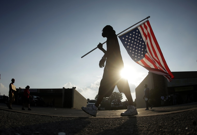 Duane Merrells walks with an upside down flag in a protest Monday, Aug. 18, 2014, for Michael Brown, who was killed by a police officer Aug. 9 in Ferguson,...