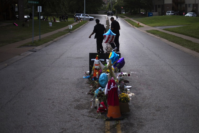 Men walk past a makeshift memorial near the site where unarmed teen Michael Brown was shot dead in Ferguson