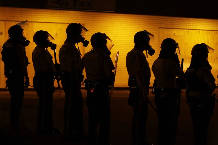 Police wait to advance after tear gas was used to disperse a crowd, Aug. 17, 2014, in Ferguson, Mo.