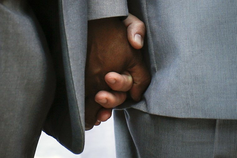 Hank Hamilton and his partner Larry Clement (L) hold hands during their same-sex marriage ceremony in a mass ceremony at Unity in Chicago in Chicago, Illinois, June 1, 2014. Same-sex marriage became legal in the State of Illinois on June 1.
