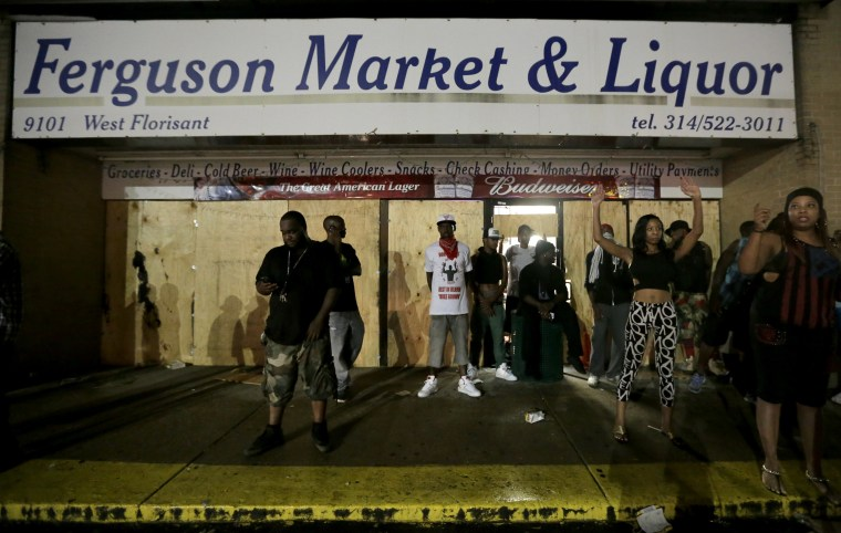 People stand in front of a convenience store after it was looted early Saturday, Aug. 16, 2014, in Ferguson, Mo. The violence stemmed from the shooting death...