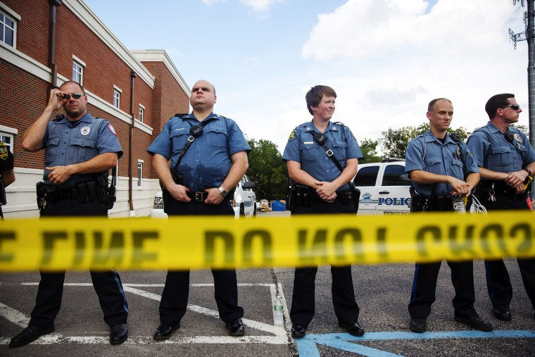 Police stand guard during a rally for Michael Brown outside the Ferguson Police Department August 30, 2014 in Ferguson, Missouri.