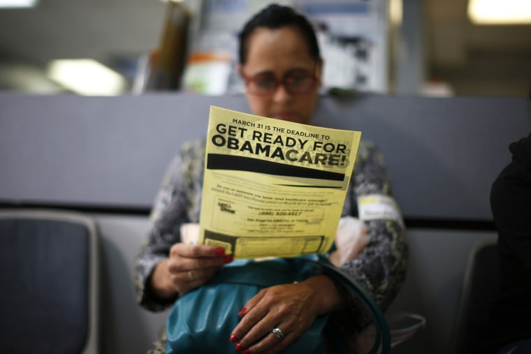 A woman reads a leaflet at a health insurance enrollment event in Cudahy, Calif., March 27, 2014