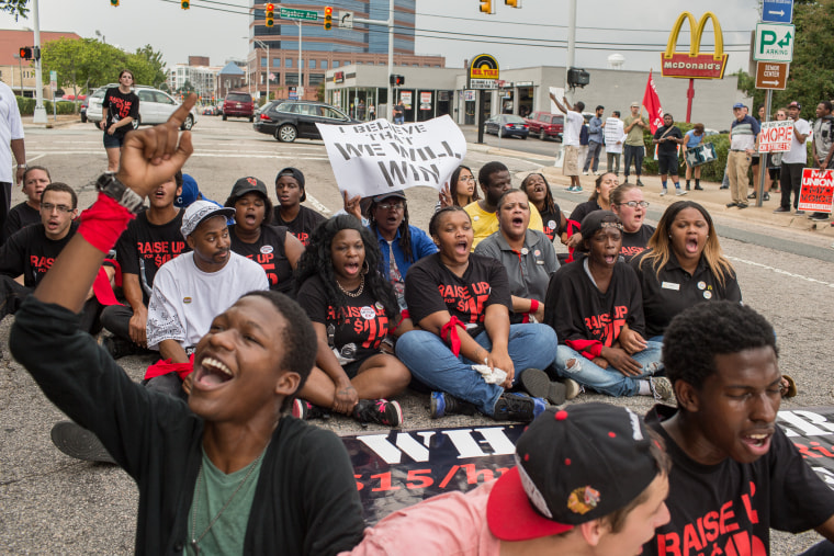 Fast food workers Darius Harris, foreground, Robert Martin, 18, and Vincent Whitehurst, 22, from Greensboro, N.C. sit in Morgan Street near Rigsbee Avenue in Durham, on Sept. 4, 2014 demanding that the fast food industry increase the minimum wage from $7.25 an hour to $15.