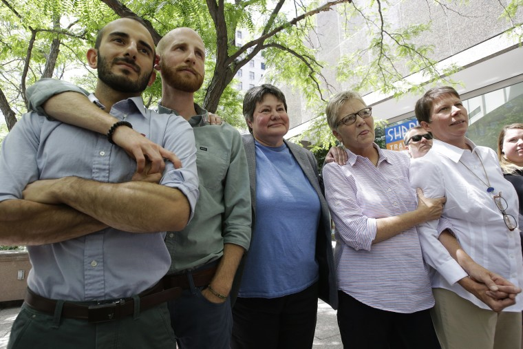 In this June 25, 2014 file photo, from left, plaintiffs Moudi Sbeity and Derek Kitchen, Kate Call, Laurie Wood and Kody Partridge, five of the six people who brought the lawsuit against the Utah's gay marriage ban, stand together at a news conference outs