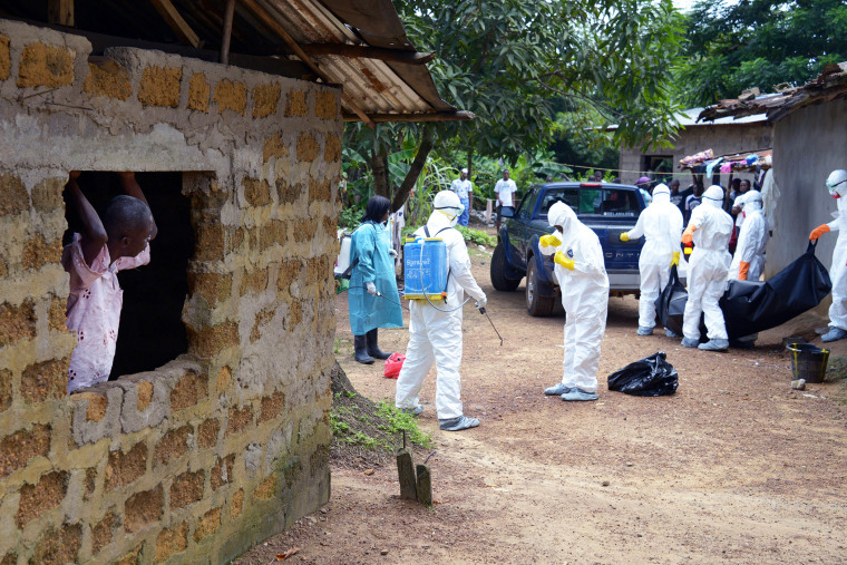 A neighbor of an Ebola virus victim looks at medical workers of the Liberian Red Cross carry his body on Sept. 4, 2014 in the small city of Banjol, 30 kilometres of Monrovia, Libera.