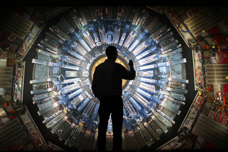 A visitor takes a photograph of an image of the Large Hadron Collider (LHC) at the  Science Museum's 'Collider' exhibition on November 12, 2013 in London, England.