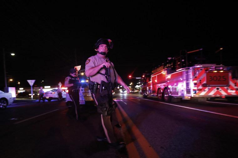 Police officers patrol a street in Ferguson