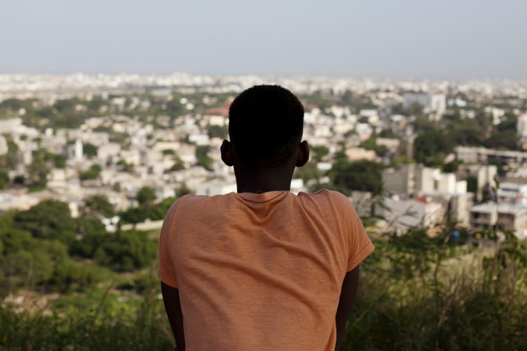 Alhaji, 21, whose last name has been withheld for his safety, looks out over Dakar as he poses for a picture near the African Renaissance Monument, in Dakar, Senegal on Oct. 23, 2013. Alhaji fled his home in neighboring Gambia last year after being beaten, tried, and persecuted for being gay.