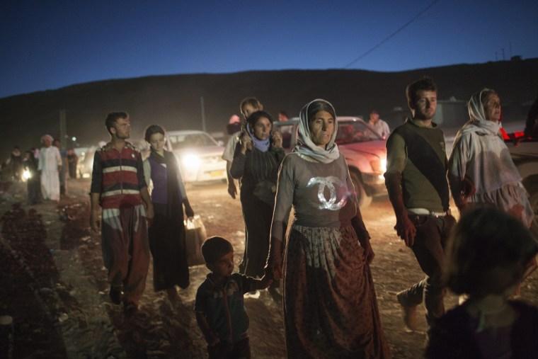 Refugees from the Yazidi religious minority cross the Syrian border into Faysh Khabur, in Iraq's northern Dohuk province on Aug. 9, 2014. (Adam Ferguson/The New York Times/Redux)