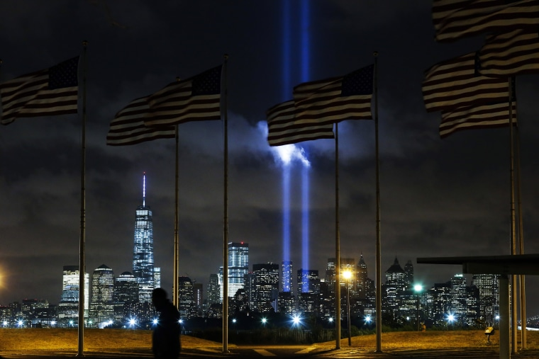 Man walks past as the Tribute in Light is illuminated on the skyline of lower Manhattan during events marking the 13th anniversary of the 9/11 attacks on the World Trade Center in New York