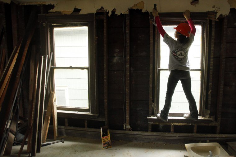 Americorps worker Yoshi Batcho helps gut a house being renovated into affordable housing by PUSH, a non-profit organization working to rebuild the West Side of Buffalo, New York, Nov. 19, 2009.