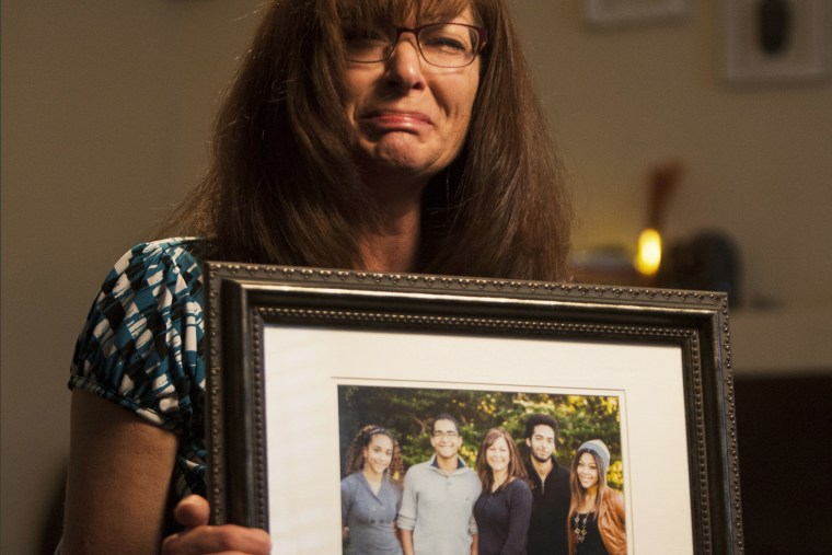 In this photo, taken, Friday, Sept. 12, 2014, shows Susan Hunt holding a photo of her family, including her son, Darrien Hunt, at her home in Saratoga Springs, Utah.
