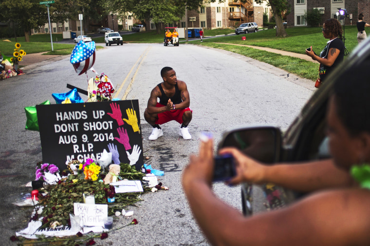 A nearby resident puts his hands together in prayer at a makeshift memorial near the site where unarmed teen Michael Brown was killed in Ferguson, Missouri, Aug. 22, 2014.