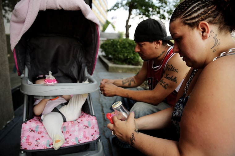 Michell and Alex, who are homeless, sit outside of the Pan Am Shelter in Queens with their daughter Alexis on Aug. 20, 2014 in New York City. (Photo by Spencer Platt/Getty)