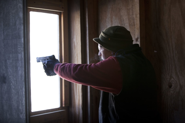 A man practices shooting his semi-automatic handgun at targets at the Ferry Brook Range, on January 26, 2013 in Keene, New Hampshire.