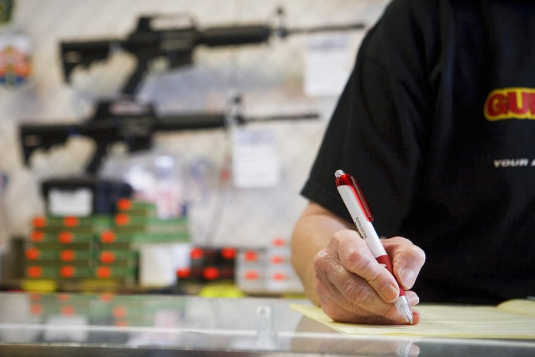 An employee reviews a customer's application as part of a background check for a handgun sale, in Houston, Texas.