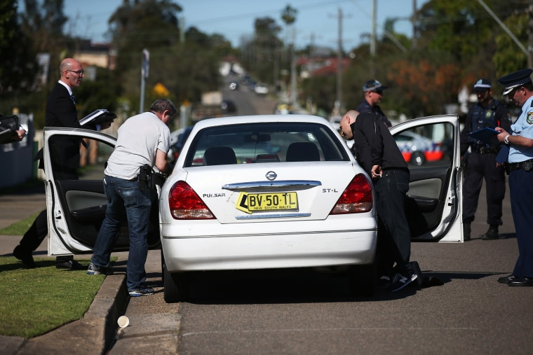 Police investigators search a car at a home at Guildford in suburban Sydney, Sept. 18, 2014.