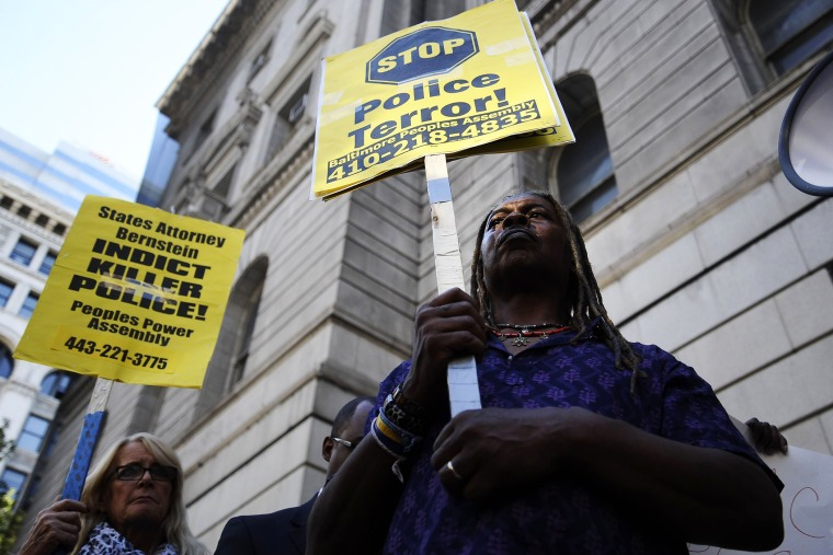 Protestors hold signs outside of the Clarence Mitchell Jr. Courthouse in Baltimore, Maryland, Aug. 14, 2014.