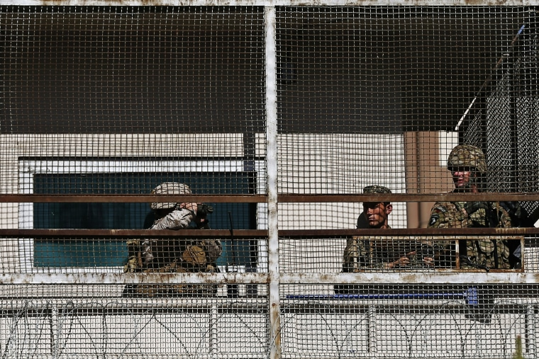 A U.S. soldier (R) and Afghan security forces keep watch from a security tower at the site of a suicide attack in Kabul September 16, 2014.