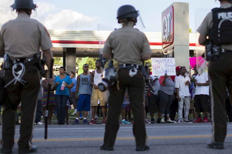 Police officers watch as demonstrators protest the death of black teenager Michael Brown in Ferguson, Mo. on Aug. 12, 2014 (Photo by Mario Anzuoni/Reuters)
